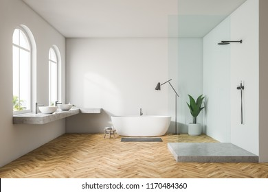 Modern white wall bathroom interior with wooden floor, arched windows, shower stall with glass door, white double sink and bathtub. Spa, hotel and luxury real estate. 3d rendering mock up