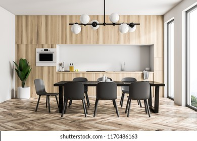 Modern white wall kitchen interior with panoramic windows, a wooden floor and countertops with built in appliances. Long black table with chairs. 3d rendering mock up
