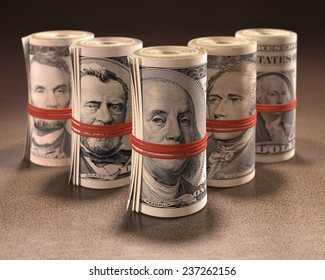 Money rolls with elastic gagging the mouths of the symbols of United States currency.