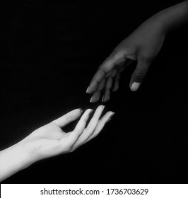 Monochromatic photo for two black & white hands with different positions showing unity, harmony, integration, and acceptance fighting against racism,prejudice, discrimination, racialism and xenophobia