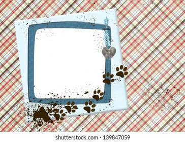 muddy paw prints from dog on blue frame with plaid background