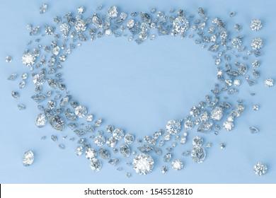 Multiple diamonds scattered in heart shaped frame on blue background. 3D illustration