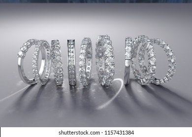 Multiple white gold diamond eternity wedding rings on gray background. 3D rendering