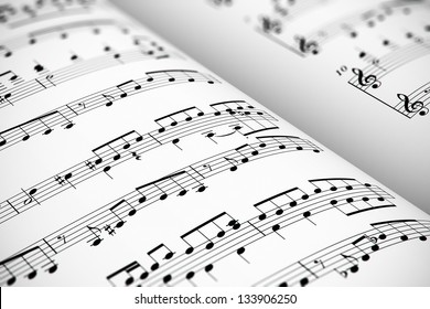 Musical concept background: macro view of white score sheet music with notes with selective focus effect