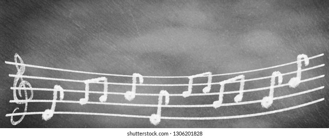 Musical staves with clef and notes on school blackboard
