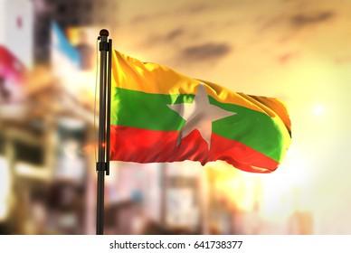Myanmar Flag Against City Blurred Background At Sunrise Backlight 3D Rendering