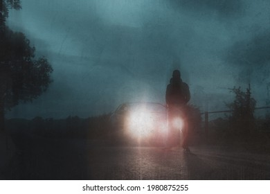 A mysterious man. Next to a car, silhouetted against car headlights On a cloudy summers evening. UK. With a grunge, artistic edit