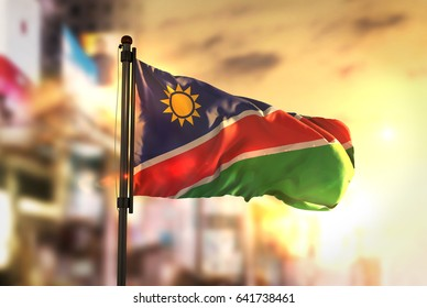 Namibia Flag Against City Blurred Background At Sunrise Backlight 3D Rendering