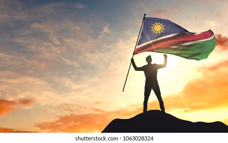 Namibia flag being waved by a man celebrating success at the top of a mountain. 3D Rendering