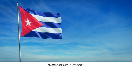 The National flag of Cuba blowing in the wind in front of a clear blue sky. 3d illustration.
