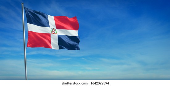 The National flag of Dominican Republic blowing in the wind in front of a clear blue sky. 3d illustration.