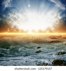 Nature background - beautiful sunrise, bright sun, sea with waves