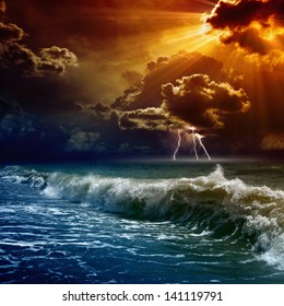 Nature force background - lightnings in dark red sunset sky, stormy sea