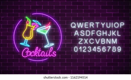 Neon cocktails bar sign with alphabet and two glasses of cocktails. Glowing gas advertising with glasses of alcohol.