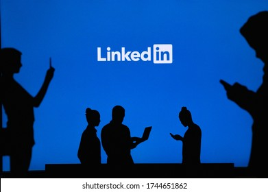 NEW YORK, USA, 25. MAY 2020: Linkedin business and employment-oriented online service Group of business people chat on mobile phone and laptop. Company logo on screen in background