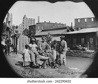 A newly freed African American group of men and a few children posing by a canal against the ruins of Richmond, Virginia. Photo made after Richmond was taken by Union troops on April 3, 1865.