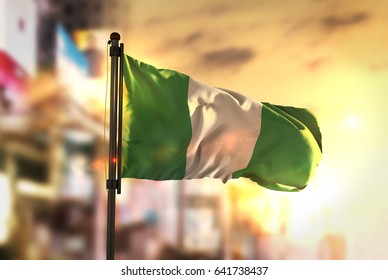 Nigeria Flag Against City Blurred Background At Sunrise Backlight 3D Rendering
