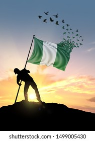 Nigeria flag turn to birds while being planted by a man on a hill during sunrise.