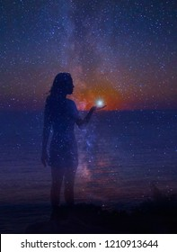 The night sky full of stars and a silhouette of a standing girl with a star in her hand. Unity of a human and universe.