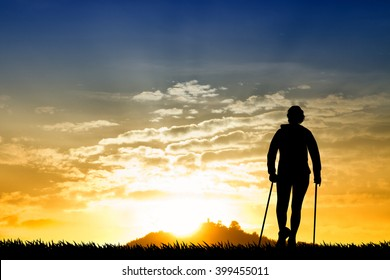 Nordic walking silhouette at sunset