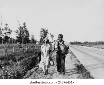 'Oakies' couple migrating. Cotton workers on the road carrying all they possess as they say 'Damned if we'll work for what they pay folks hereabouts.' Crittenden County Arkansas May 1936.