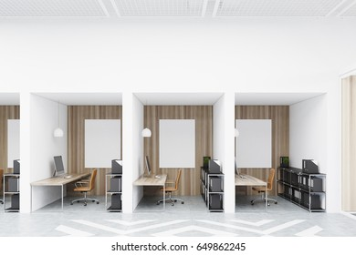 Office cubicles in an office with white and wooden walls and diamond floor pattern. There are blank vertical pictures in each of them, a desk with a computer, a chair and shelves. 3d rendering mock up