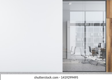Office hall with white, glass and wooden walls, concrete floor, open space area with rows of computer desks and bookcases and mock up wall on the left. 3d rendering