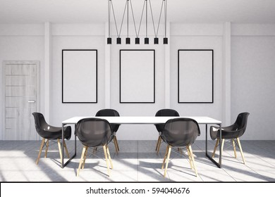 Office meeting room interior with three framed vertical posters hanging on a white wall, a row of ceiling lights and a table surrounded by black armchairs. 3d rendering, mock up
