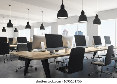 Office of a modern company with white walls, a concrete floor, large windows and a long wooden table with computers on them. A side view 3d rendering mock up
