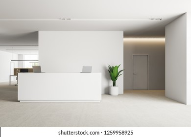 Office reception area with white walls, carpet on the floor, white reception desk with laptops and a door to the right. 3d rendering