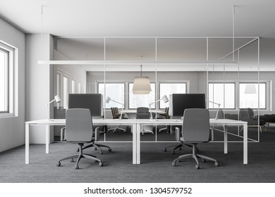 Office workplace interior with white walls, carpeted floor, white computer tables with gray chairs and meeting room in background. 3d rendering