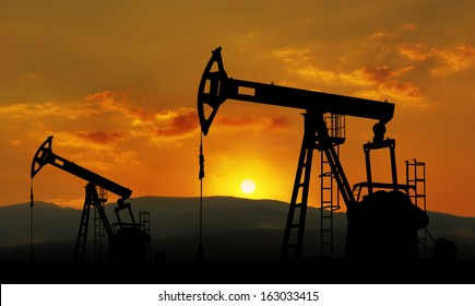 oil field and pump jack against sunset