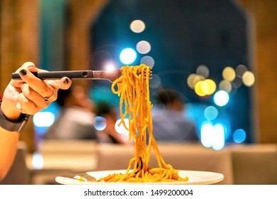 Oil paint of Spaghetti roll on a fork. Hand of woman rolling spaghetti and keep on a fork. Beautiful colorful and light bokeh at night. Design for wallpaper, backdrop or background in the restaurant.