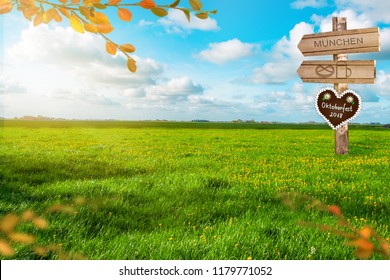 Oktoberfest 3d illustration. Beautiful green meadow and a signpost with gingerbread heart. October party background.