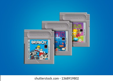 Old Gameboy Classic games isolated on the blue background, Tetris, Paperboy and The Simpsons video game cartridges.