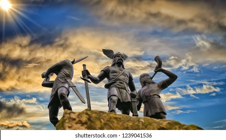 Old Norse God Odin on a rock, flanked by two Vikings, one of them raised a sword and the other is trumpeting with horn, blue sky, bright sun, clouds, painting style illustration
