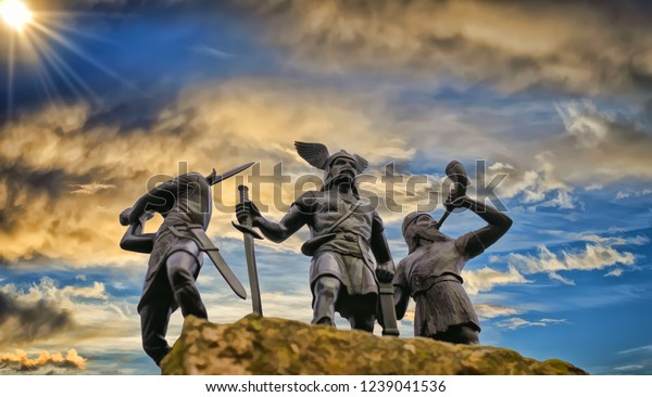 Viejo Dios Odin sobre una roca, flanqueado por dos vikingos, uno de ellos levantó una espada y el otro está tropezando con cuerno, cielo azul, sol brillante, nubes, ilustración de estilo pintado