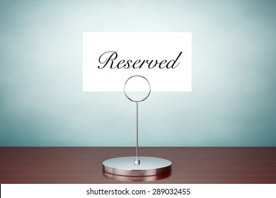Old Style Photo. Note Paper Card Holder with Reserved Sign on the table