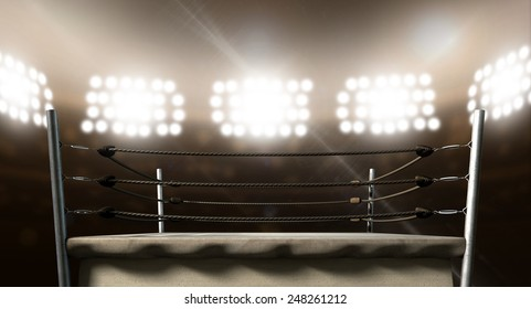 An old vintage boxing ring surrounded by ropes spotlit by floodlights in an arena setting at night