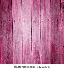 Old  wooden vertical planks background with pink paint cracked