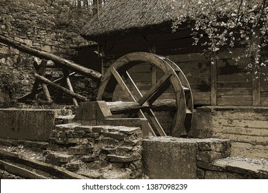 Old wooden water mill in a rural courtyard.