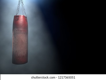 An old worn red leather punching bag hanging by chains in a 