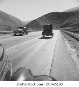 On U.S. 99. in Kern County on the Tehachapi Ridge. Migrants in an old car travel on the three lane highway between Imperial Valley and the San Joaquin Valley. Feb. 1939 photo by Dorothea Lange.