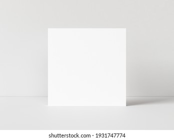 One blank square poster template standing on white table with white background. 3D illustration