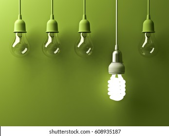 One hanging energy saving light bulb glowing different stand out from unlit incandescent lightbulbs with reflection on green background , leadership and different creative idea concept . 3D rendering.