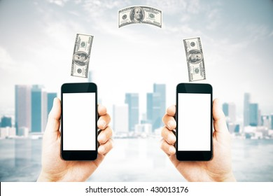 Online money transfer concept with two male hands holding smart phones with blank white screens and dollar bills above on city background. Mock up, 3D Rendering