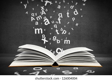 open book with letters on concrete background