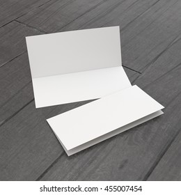 open and closed two-leaf brochures or greeting cards on wooden flloor. 3D rendering