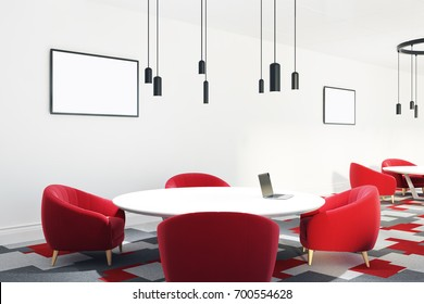 Open office room with a group work area with a large round table and red armchairs. Posters on the wall. 3d rendering mock up
