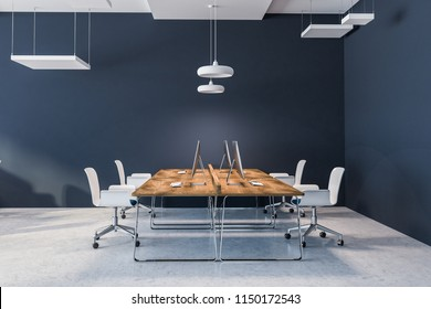 Open space office interior with dark blue walls, a concrete floor, rows of wooden computer desks and white chairs. 3d rendering mock up